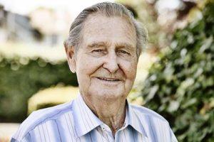 Man smiles outside independent senior living center.