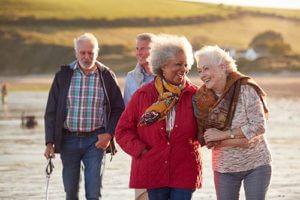 seniors walking along the beach during boynton beach florida senior living activities