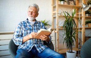 Man reads book at Discovery Village Senior Independent Living.
