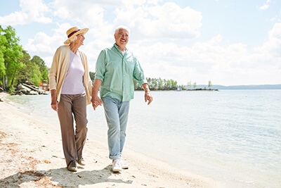 senior couple holding hands walking along the beach for senior living activities