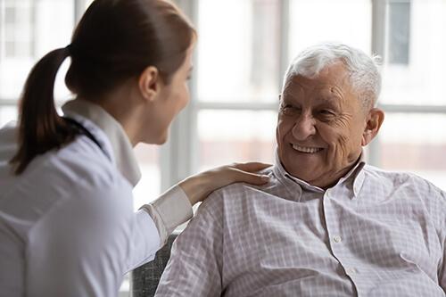 Caring geriatric nurse in white coat cares for elderly man